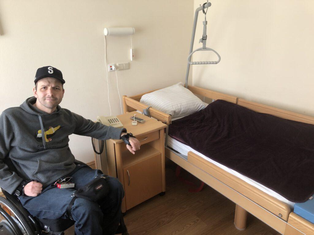 Bild zeigt mich vor einem Pflegebett im Pflegeheim